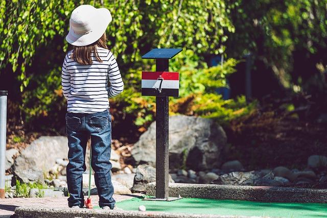 jente spiller minigolf